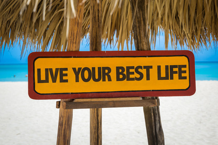 mentality: Wooden sign board in beach with text: Live your best life