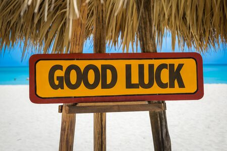 Wooden sign board in beach with text: Good luck