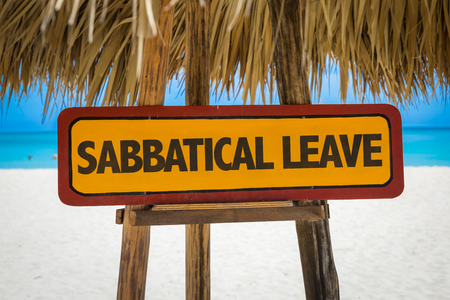 Wooden sign board in beach with text: Sabbatical leave