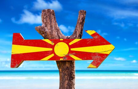 Macedonia flag sign with arrow on beach background