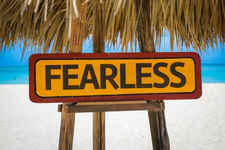unafraid: Wooden sign board in beach with text: Fearless Stock Photo