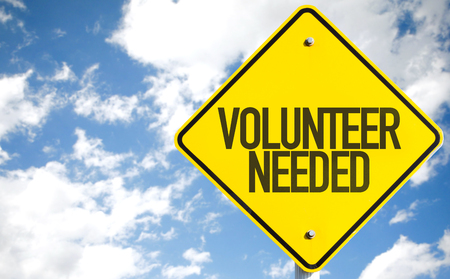 Volunteer needed sign with clouds and sky background Stock Photo