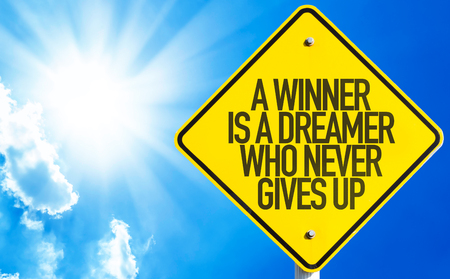 A winner is a dreamer who never gives up sign with sunny background Stock Photo