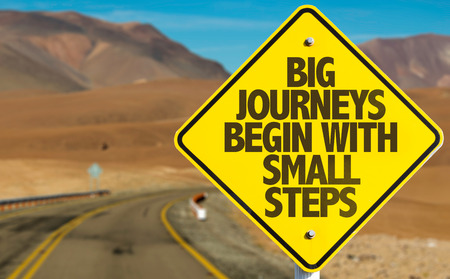 Big journeys begin with small steps sign on a highway background