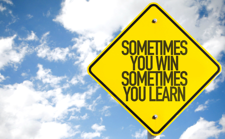 Sometimes you win sometimes you learn sign with clouds and sky background