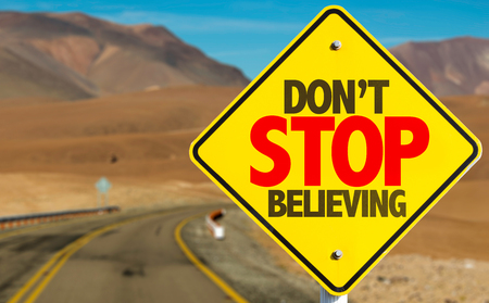 believing: Dont stop believing sign on a highway background