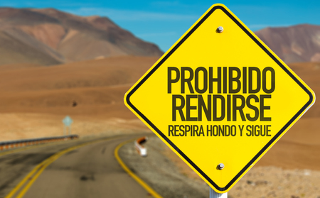 hondo: Prohibido rendirse respira hondo y sigue (dont surrender, take a deep breath and keep going in Spanish) sign on a highway background Stock Photo