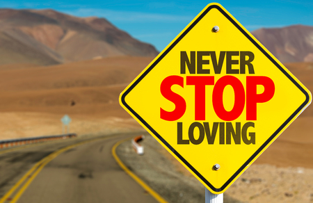 Never stop loving sign on a highway background Stock Photo