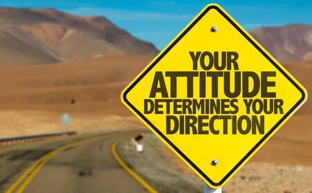 determines: Your Attitude Determines Your Direction sign on desert road