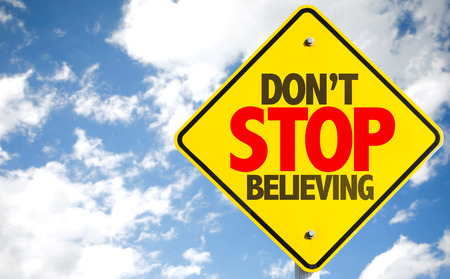 believing: Dont Stop Believing sign with sky background Stock Photo