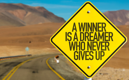 persevere: A Winner Is A Dreamer Who Never Gives Up sign on desert road