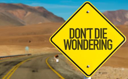 wondering: Dont Die Wondering sign on desert road Stock Photo