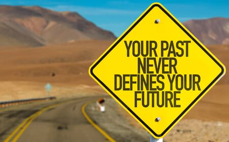 defines: Your Past Never Defines Your Future sign on desert road