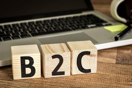 b2c: B2C written on a wooden cube in front of a laptop