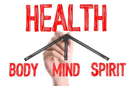 actividad fisica: Mano con marcador de escribir la palabra salud - BodyMindSpirit Foto de archivo