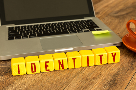 thieving: Identity written on a wooden cube in front of a laptop Stock Photo