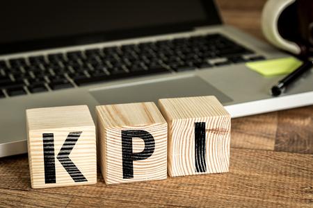 노트북 앞에 나무 큐브에 기록 된 KPI 핵심 성과 지표