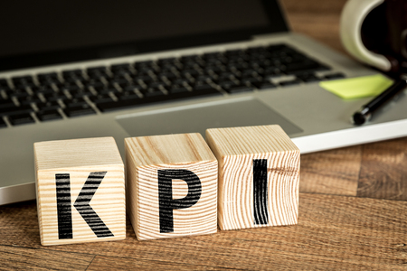 KPI Key Performance Indicator written on a wooden cube in front of a laptop