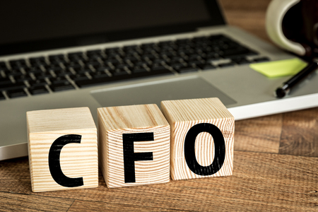 comit� d entreprise: CFO Chief Financial Officer written on a wooden cube in front of a laptop
