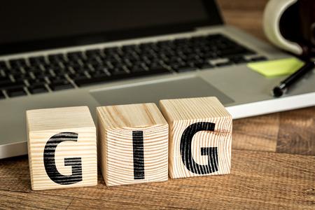 GIG geschreven op een houten kubus in de voorkant van een laptop