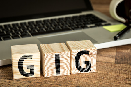 gig: GIG written on a wooden cube in front of a laptop
