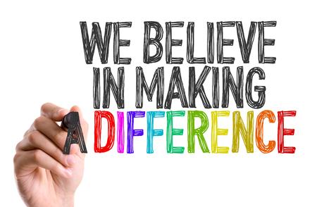 comunidad: Mano con la escritura marcador: Creemos en hacer una diferencia