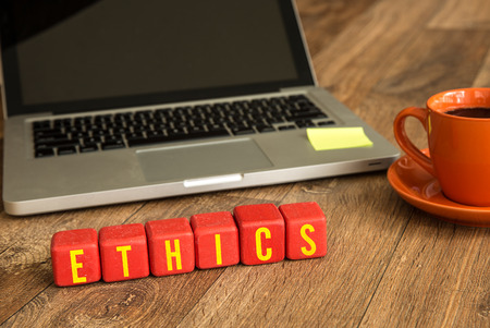 normative: Ethics written on a wooden cube in front of a laptop