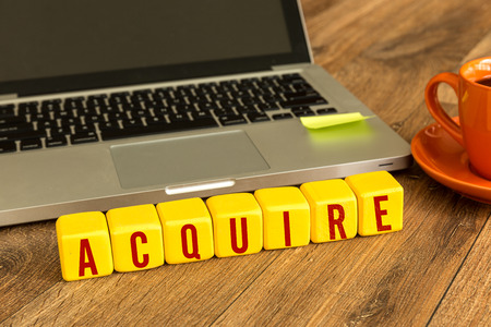 acquire: Acquire written on a wooden cube in front of a laptop Stock Photo