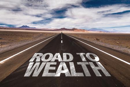 Road to Wealth scritto su strada del deserto