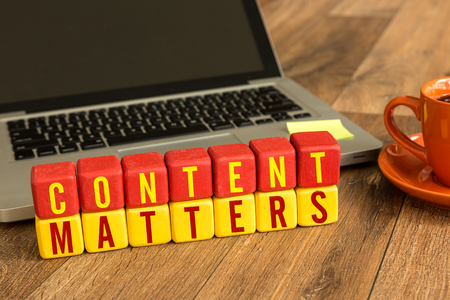 content management: Content Matters written on a wooden cube in front of a laptop