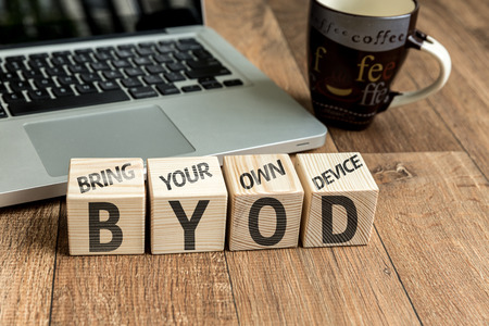 own: Bring Your Own Device BYOD written on a wooden cube in front of a laptop