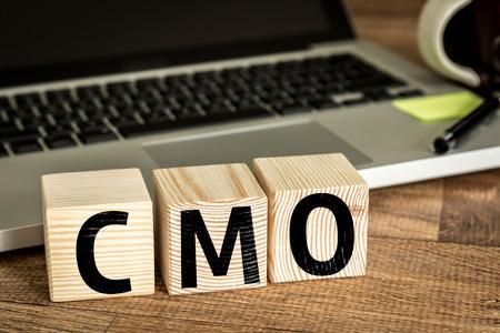 CMO Chief Marketing Officer geschreven op een houten kubus in de voorkant van een laptop Stockfoto