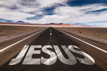 Jesus written on desert road Stock Photo