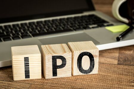 initial public offerings: IPO Initial Public Offering written on a wooden cube in front of a laptop