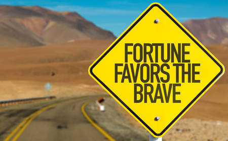 positive: Fortune Favors the Brave sign on desert road Stock Photo