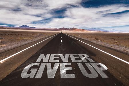 Never Give Up scritto su strada del deserto Archivio Fotografico - 49104204