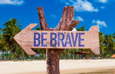 brave: Be Brave arrow with beach background Stock Photo