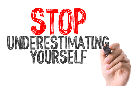 lower value: Hand with marker writing the word Stop Underestimating Yourself