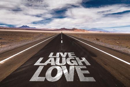 success word: Live Laugh Love written on desert road