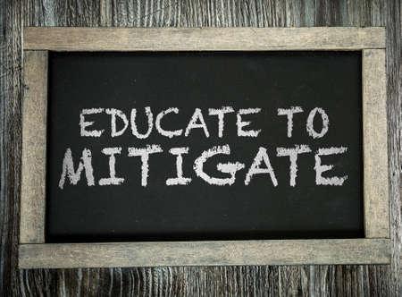 mitigate: Educate to Mitigate written on chalkboard Stock Photo