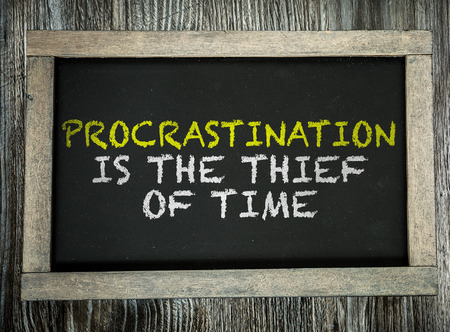 procrastination: Procrastination is the Thief of Time written on chalkboard