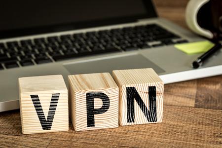 VPN Virtual Private Network geschreven op een houten kubus in de voorkant van een laptop Stockfoto