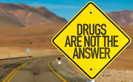 street drug: Drugs Are Not the Answer sign in a deserted road