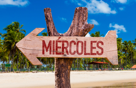 wednesday: Wednesday in Spanish arrow with beach background Stock Photo