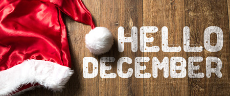 Hallo december geschreven op houten achtergrond met kerstmuts Stockfoto