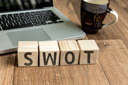 SWOT written on a wooden cube with laptop background