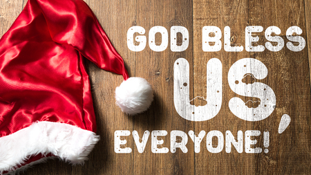 God bless us, everyone! written on wooden background with santa hat Stock Photo