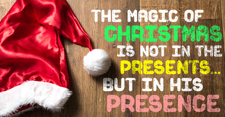 The magic of Christmas is not in the presents%u2026but in His presence written on wooden background with santa hat