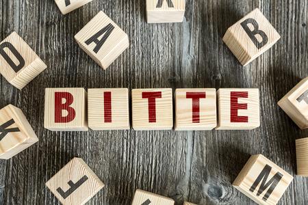 cordiality: Bitte (please in German) written on a wooden cube background