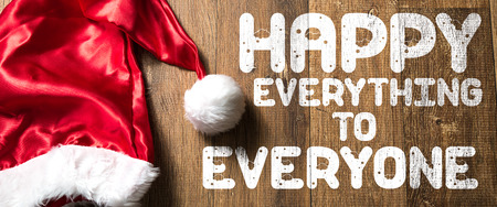 Happy everything to everyone written on wooden background with santa hat Stock Photo
